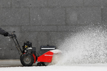 A man uses a snow blower to clean a sidewalk in the Long Island City section of Queens