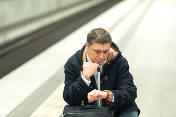 Crouched man waiting for the train and checking the time