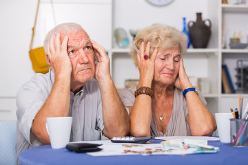 Upset retired couple calculating domestic finances