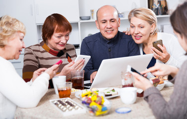Mature women and their friend are looking at notebook and talking