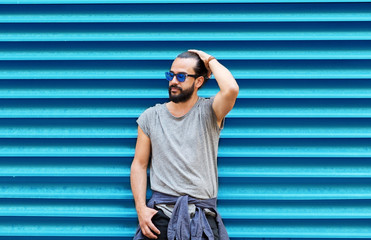 man in sunglasses posing over ribbed blue wall