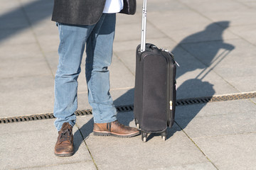 Cropped image of male legs and black trolley suitcase. Outdoors