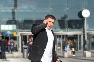 Busy businessman talking on mobile phone waiting a taxi. Outdoors