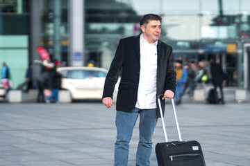 Portrait of traveler with luggage. Outdoors