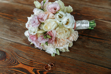 Wedding bouquet of cream and pink roses lies on a wooden surface. Wedding rings