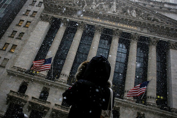 A woman stops to photograph the NYSE as snow begins to fall during the morning commute in New York