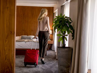 Young businesswoman arrives in a hotel room with red suitcase