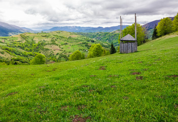 old wooden hay shed on grassy hillside