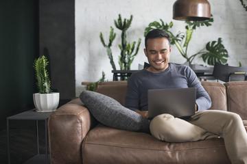 Asian man looking at the computer at home.