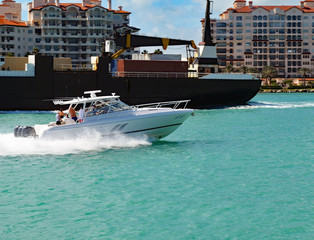 Sport fishing boat powered by three outboard engines heading towards port of miami with sightseeing passengers aboard.