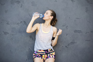 Young athletic woman drinking water by the wall