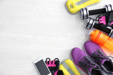 Gym stuff, mobile phone and blank space for exercise plan on wooden background. Flat lay composition
