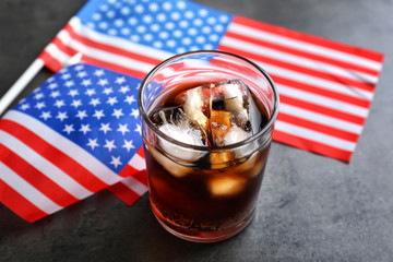 Glass of cold cola with flag of the USA on grey background