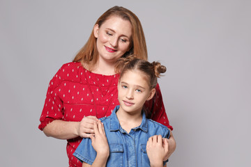 Portrait of happy mother and daughter on grey background