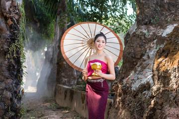 Beautiful Lao girl in laos costume holding umbrella.