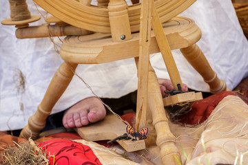 old woman using an old wool spinning wheel