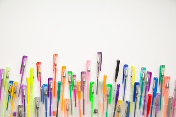 Bright, colorful pens on a white background shot overhead.