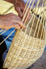 Man's hands making a wicker basket under sunny day