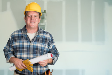 Contractor with Plans and Hard Hat In Front of Drywall. Wall mural