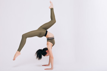 Gymnast girl performs stretching exercises on the white background