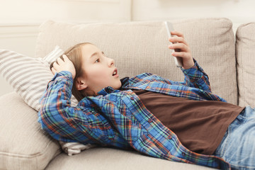 Young shocked girl with smartphone at home