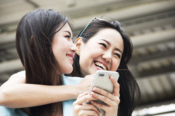 Beautiful women happy for playing on mobile phone.
