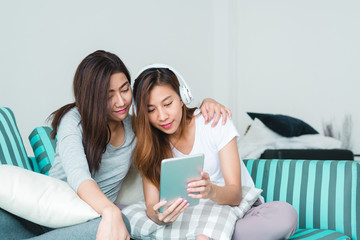 Beautiful young asian women LGBT lesbian happy couple sitting on sofa buying online using tablet in living room at home. LGBT lesbian couple together indoors concept. Spending nice time at home.