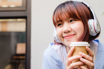 Happy young Asian woman listening to music in a coffee shop holding a cup of coffee in her hand. Young Woman listening to music with headphone while relaxing in the garden. Coffee relax concept.