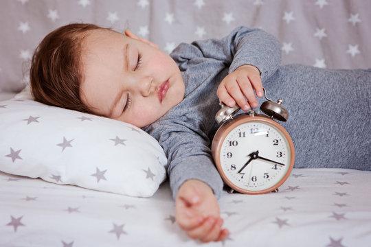 baby sleeping in a crib with an alarm clock