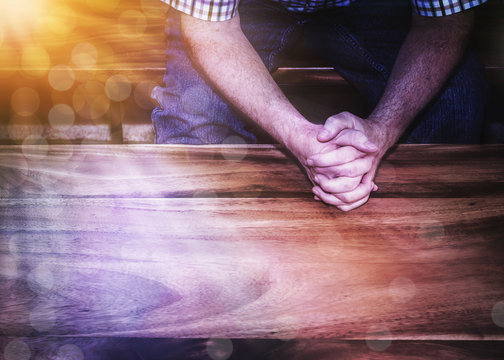 A man hands pray over wooden table with Bokeh light effected, copy space