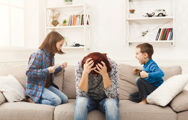 Kids having quarrel over tired mother