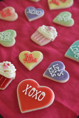 Colourful, iced cookies on red material, close-up