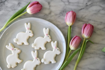 Iced, rabbit shaped cookies, on white plate, with pink tulips, overhead view