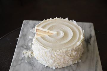 White frosted cake, with slice missing, elevated view