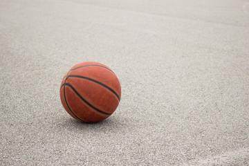 Used orange leather basketball on grey asphalt background.