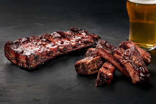 Pork ribs in barbecue sauce and a glass of beer on a black slate dish. A great snack to beer on a dark stone background. Top view with copy space