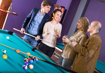 Adults with wine at billiard table.