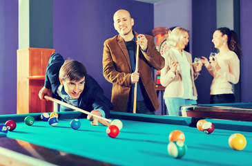 Relaxed positive smiling people playing billiard and darts