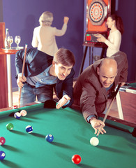 Group of friends playing billiards