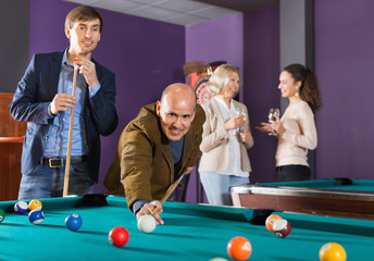 Group of cheerful friends playing billiards