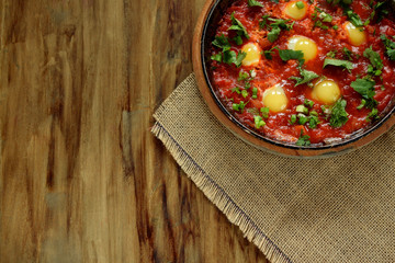 Fried eggs with tomato sauce and parsley in a cast iron pan. Shakshuka a traditional meal of the Jewish cuisine