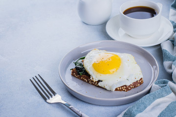 Rye bread toasts with fried spinach and egg with cup of coffee and orange juice on blue table background. Healthy Breakfast Food Concept. Copy Space