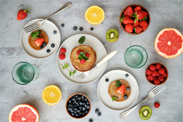 Breakfast table with pancakes, berries and fruits. Top view, gray light background