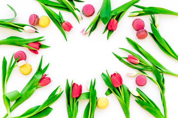 Spring gift. Flowers and sweets. Tulips and sweets macarons on white background top view copy space