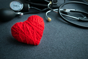 Red thread heart with tonometer on grey table.  Sphygmomanometer, doctor workplace. Blood Pressure Monitor. Medical equipment. Cardiac diagnosis