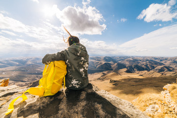 woman tourist with a yellow backpack sitting on a background of mountains on a sunny day