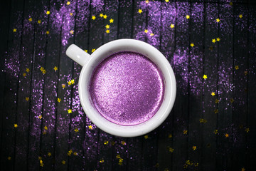 Cup of coffee with purple glitter on dark background with golden stars. Glitter cappuccino, sparkly shine  gold espresso, coffee with sparkle. Trendy drink, original concept. Holiday party background.