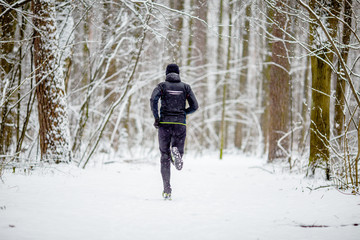 Picture from back of man in sports clothes on run in winter