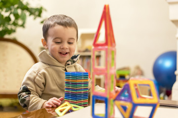 happy smiling boy playing with magnetic constructor toy