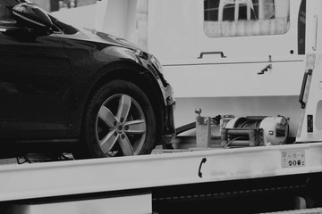 New car transported on tow track in b/w format